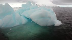 Ice movement icebergs of global warming floats in ocean of Antarctica. Amazing unique beautiful wilderness nature and landscape of snowy mountains. Extreme stock video footage
