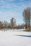 Ice on the Olympiapark Lake. With Skaters and BMW Building Stock Images