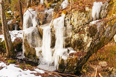 Ice overhangs on rocks Stock Photography