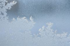 Ice patterns on the window during strong frost. Flowers, lines, crystals, ice rose, abstract pattern Stock Photos