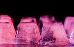 Ice. Pieces, it is red pink color on a black background Stock Photography