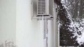 Ice pile frozen under heat pump system on house wall in winter. Zoom in. 4K stock video