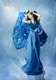 Ice Princess. The girl in a long blue dress surrounded by shards of ice and by icicles, while standing on the ice surface.Ice Princess stock photos
