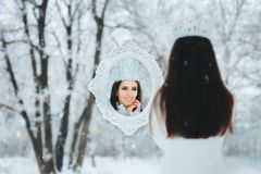 Snow Queen Looking in Magic Mirror Winter Frost Fantasy Portrait. Ice princess and her mirror of reason checking her reflection Royalty Free Stock Photo