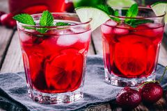 Ice refreshing cherry lemonade in glass with ice cubes, lime and mint. Iced refreshing cherry lemonade in glass with ice cubes, lime and mint on a wooden Royalty Free Stock Photography
