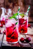 Ice refreshing cherry lemonade in glass with ice cubes and mint. Iced refreshing cherry lemonade in glass with ice cubes and mint on a wooden background Stock Images