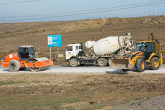 Ice Rink, cement mixer and excavator are on the road leading to the bridge being built Kerch Royalty Free Stock Photo