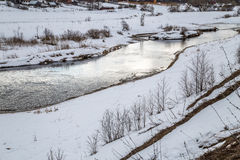 Ice on the river had already melted. The snow still lies on the banks of the cloudy sky Stock Photography
