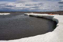 Ice on the river and orange kayak. Stock Photography