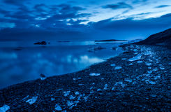 Ice on rocky shores at twilight Royalty Free Stock Photography