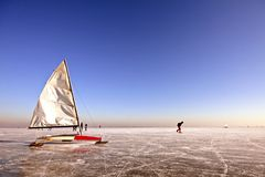 Ice sailing and skating on a cold winterday. Traditional dutch: Ice sailing on a cold winterday on the Gouwzee in the Netherlands Royalty Free Stock Photo