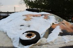 Ice salt covered by canvas, snow and tire. This is a pile of Ice salt covered by canvas, snow and tire stock photo