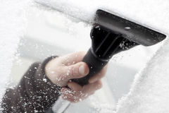 Ice scraper. Scraping snow and ice from the car windscreen Royalty Free Stock Image