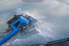 Ice scraper cleaning a frozen windshield of a car, winter traffi Stock Image