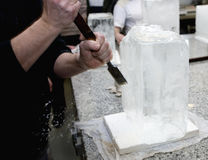 Ice sculptor. Sculptor on ice cube to get a nice design, beginning of the work Royalty Free Stock Photo