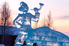 Ice sculpture - a man with a hunting horn and a bear on the background of the dawn. Russia, Surgut, December 20, 2018: Historical and cultural center `Old Surgut stock photo