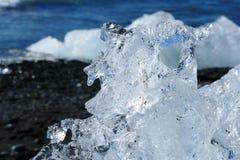 Ice sculpture in sunshine on Diamond Beach, Jökulsárlón glacier lagoon, Iceland royalty free stock photos