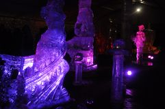 Ice sculptures in blue and purple lights at night