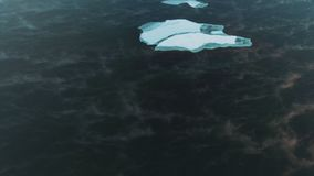 Ice shard float in the dark water. Aerial view ice drift. Large ice floe sails in the midst of dark water, shot from above. ice drifts in open water, a stock video