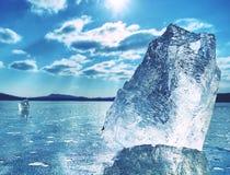 Ice shards on a frozen lake. The rays of the sun creat rainbow shadows Stock Photography