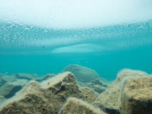 Ice sheet covers shallow lake rock bottom Stock Images