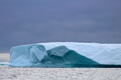 Ice shelf, Antarctica. The vibrant teal underside and pristine white of an Antarctic iceshelf contrasts the darkening pre-storm sky Royalty Free Stock Images