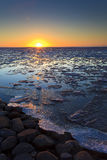 Ice shelves at sunset on a frozen lake. Ice shelves at sunset with the sun at the horizon and a blue sky on a frozen lake in Holland Stock Photo