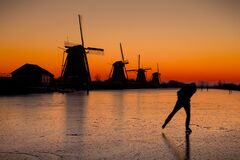Free Ice Skater In Front Of The Kinderdijk Windmills Stock Photography - 214647592