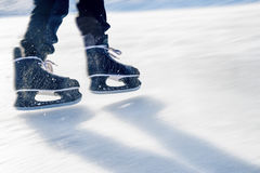 Ice skater`s feet on ice rink Royalty Free Stock Photography