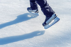 Ice skater`s feet on ice rink Royalty Free Stock Image