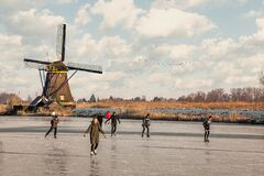 Ice skaters on a frozen windmill canal at sunrise moment