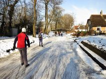 Ice skaters in frozen winter landscape in Holland. Giethoorn, Netherlands - February 6, 2012. Ice skaters in Dutch winter landscape Royalty Free Stock Photo