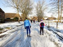 Ice skaters in winter landscape in snowy Holland. Giethoorn, Netherlands - February 6, 2012. Ice skaters in Dutch winter landscape Royalty Free Stock Images