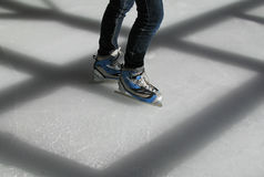 Ice skates. And legs of a skater. Shadows of the shelter's timbers casts across the ice Stock Photography