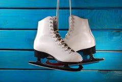 Ice skates on blue wooden background Royalty Free Stock Image