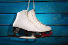 Ice skates on blue wooden background Royalty Free Stock Image