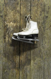 Ice skates hanging on an old weathered wooden wall. White ice skates hanging on an old weathered wooden wall Stock Photos