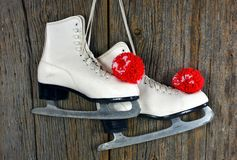 Ice skates and red yarn pompoms Royalty Free Stock Image