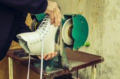 Ice skates sharpening. White ice skates sharpening at machine royalty free stock images