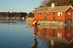 Ice skating. A woman skating in front of a building in the Stockholm archipelago, Sweden stock image