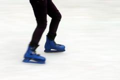 Ice skating. Ice skater gliding on ice with blue ice skates Stock Photos