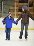 Ice skating. Young mother and son ice skating at indoor rink Stock Photo