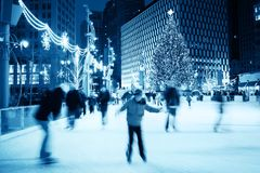 Ice Skating at Christmas. In camera motion blur of ice skaters in an urban ice skating rink Royalty Free Stock Photo