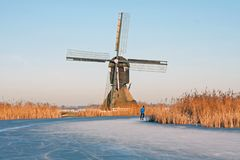 Ice skating in the countryside from the Netherlands in winter. Ice skating in the countrye from the Netherlands in winter at a traditional windmill Stock Photography