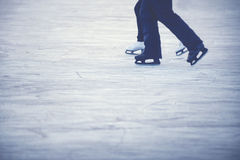 Ice skating couple. Legs of woman and man with white and black skates Stock Image