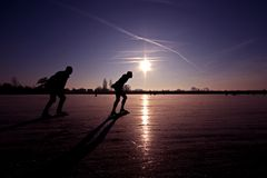 Ice skating on a frozen lake in the Netherlands. With a beautiful purple sunset Stock Photo