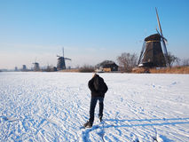 Ice skating in Holland. Person having fun while ice skating on a frozen canal along windmills at the Unesco World Heritage Site Kinderdijk in the Netherlands in Stock Image