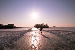 Ice skating in the Netherlands. Ice skating on the Gouwzee in the Netherlands at sunset Stock Photo