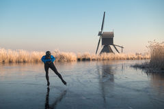 Ice skating past frosted reeds and a windmill. Person ice skating alone on a frozen river past a windmill and hoar frosted reeds in Kinderdijk in winter in the Royalty Free Stock Photography