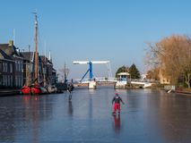 Ice skating during sunny winter day on natural ice in Friesland, stock image